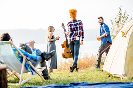 Multi ethnic group of friends dressed casually having fun during the outdoor recreation at the camping near the lake
