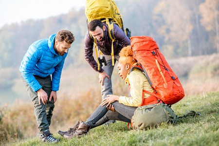 Young african woman with backpack having a trauma with knee hiking with friends outdoors