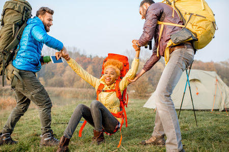 Young male hikers helping woman to get up staning with colorful backpacks on the green lawn near the camping place Stock Photo