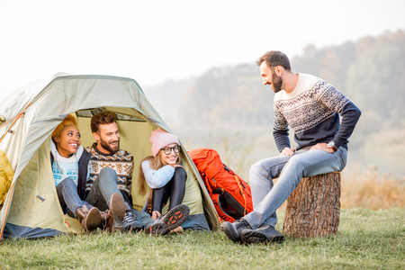 Multi ethnic group of friends dressed in sweaters warming up together sitting during the outdoor recreation near the tent Stock Photo - 89781854