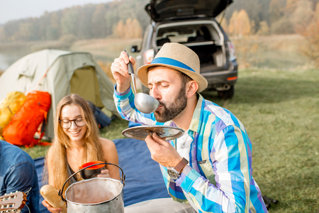 Multi ethnic group of friends dressed casually having a picnic, cooking soup with cauldron during the outdoor recreation with tent, car and hiking equipment near the lake