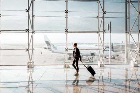 空港の出発ホールでスーツケースを持って歩いている女性と、お越しの窓に表示されます。コピースペースを使用した広角ビュー