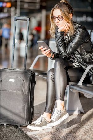 Young business woman in leather jacket and pants sitting with phone and suitcase at the departure hall of the airport waiting for the flight