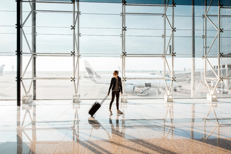View on the aiport window with woman walking with suitcase at the departure hall of the airport. Wide angle view with copy space Stock Photo
