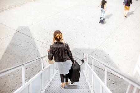 Frau, die unten mit Koffer auf der Flugzeugtreppe, Draufsicht über den Grundhintergrund geht.