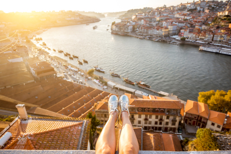 Female legs on the beautiful landscape view background during the sunset in Porto city, Portugal