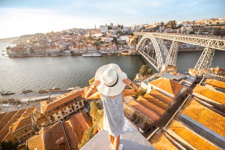 Tourist der jungen Frau, der schöne Landschaftsansicht über die alte Stadt mit Fluss und berühmter Eisenbrücke während des Sonnenuntergangs in Porto-Stadt, Portugal genießt
