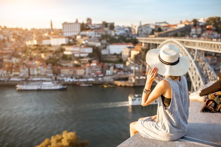 포르토 도시, 포르투갈에서에서 일몰 동안 강와 유명한 철 다리로 오래 된 마을에서 아름 다운 풍경보기를 즐기는 젊은 여자 관광