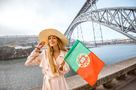 Portrait of a young woman traveler with portuguese flag on the famous iron bridge background in Porto city Stock Photo