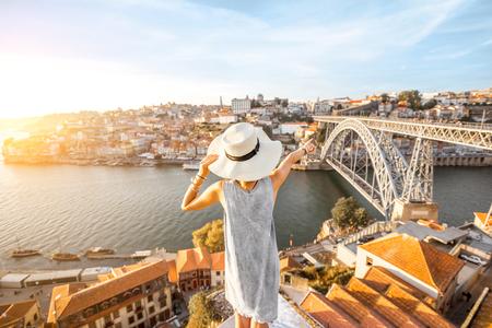 Jonge vrouwentoerist die mooie landschapsmening over de oude stad met rivier en beroemde ijzerbrug genieten tijdens de zonsondergang in Porto stad, Portugal Stockfoto