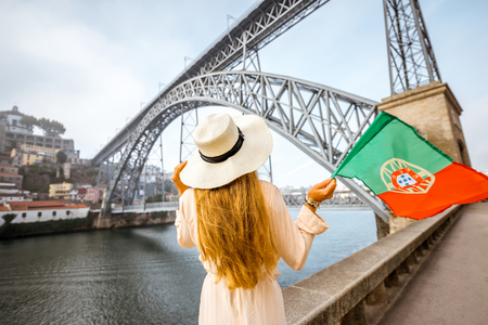 Young woman traveler in sunhat standing back with portuguese flag with the famous iron bridge on the background in Porto city Banco de Imagens - 89001161