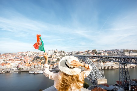 bandera de portugal: Young woman traveler with portuguese flag standing back on the beautiful cityscape background with Douro river and Luise bridge during the morning light in Porto, Portugal Foto de archivo