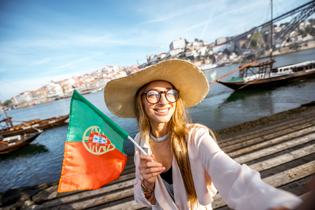 bandera de portugal: Young woman tourist making selfie portrait with portuguese flag on the beautiful landscape background during the morning light in Porto city, Portugal Foto de archivo