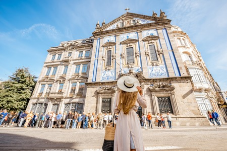 Young woman tourist standing near the Congregados church with famous portuguese blue tiles on the facade traveling in Porto city. Portugal