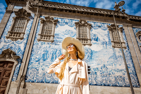 Young woman tourist standing near the church with famous portuguese blue ceramic tiles on the facade traveling in Porto city, Portugal