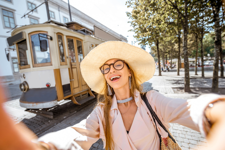 tramway: Lifestyle portrait of a woman near the famous old touristic tram on the street in Porto city, Portugal Stock Photo