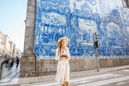 Young woman tourist walking near the church with famous portuguese blue ceramic tiles on the facade traveling in Porto city, Portugal