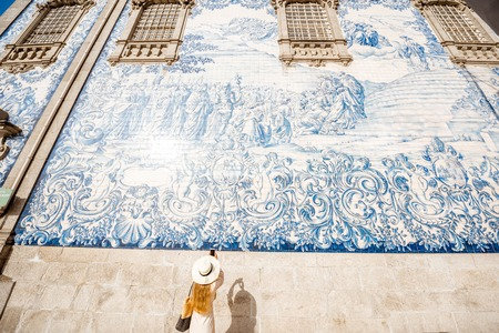 Young woman tourist photographing famous portuguese blue ceramic tiles on the facade traveling in Porto city, Portugal