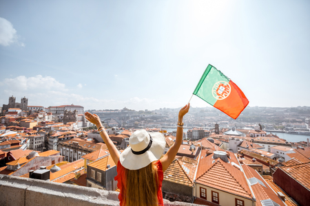 Young woman tourist in red dress standing back with portuguese flag on the old town background traveling in Porto city, Portugal