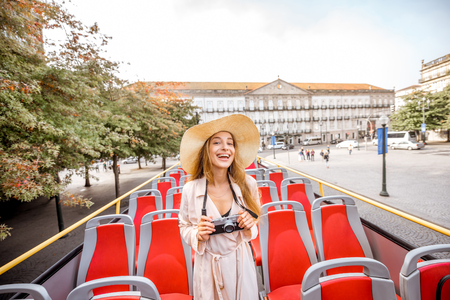 Happy woman having excursion on the open touristic bus standing on the Liberty square in Porto city, Portugal Stock Photo