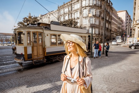 Lifestyle portrait of a woman with photo camera near the famous old touristic tram on the street in Porto city, Portugal