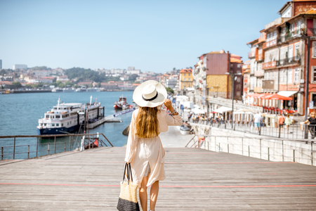 Young woman tourist walking on the Ribeira promenade of Porto cuty during the sunny day in Portugal Imagens