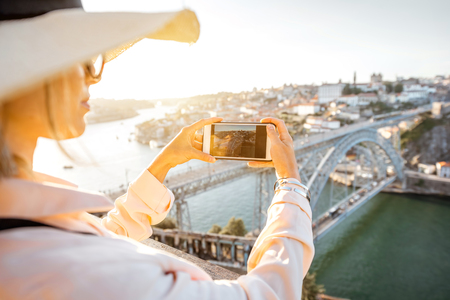 Young woman tourist enjoying beautiful aerial cityscape view with famous bridge during the sunset in Porto city, Portugal Stock Photo