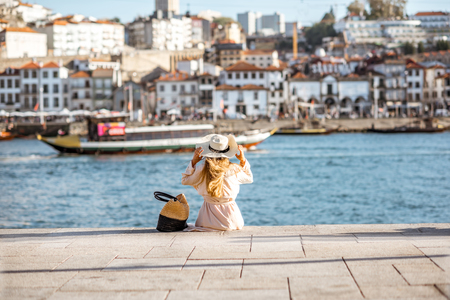 Young woman tourist sitting back on the Ribeira promenade enjoying cityscape view on the Porto city during the sunny day in Portugal