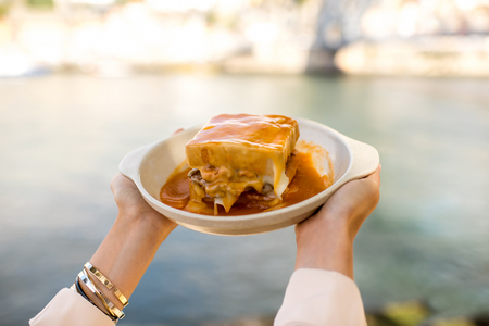 Holding a plate with traditional portuguese sandwich with meat called francesinha on the landscape background in Porto city, Portugal