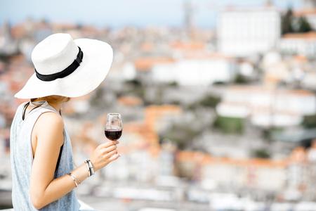 ポルトガルのポルト市の素晴らしい街並みを望むテラスでポルトワインのグラスと一緒に座る若い女性観光客