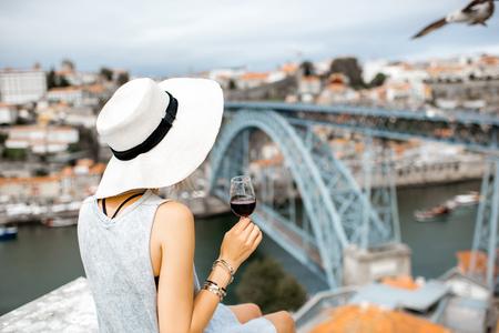 ポルト ワインのグラスとポルトガル ポルト市の都市景観の素晴らしい景色を望むテラスに座っている若い女性観光客