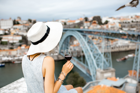 Young woman tourist sitting with glass of Porto wine on the terrace with great cityscape view on Porto city in Portugal Standard-Bild