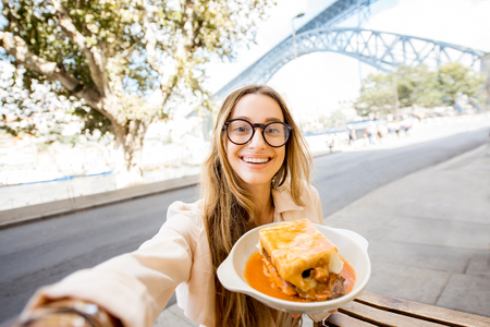 Young woman enjoying traditional portuguese meat sandwich called Francesinha, sitting at the bar with famous bridge on the background in Porto city, Portugal