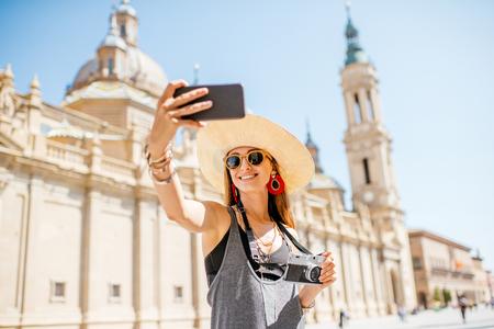 Jonge vrouwentoerist die selfie foto voor de beroemde kathedraal op het centrale vierkant tijdens het zonnige weer in Zaragoza-stad, Spanje maken