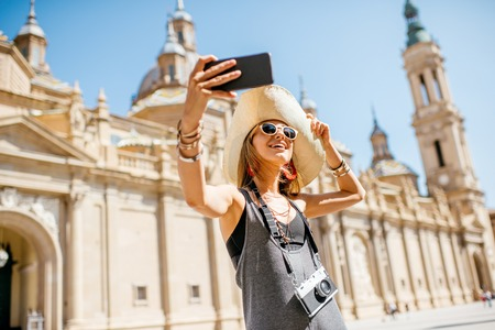 sunhat: Young woman tourist making selfie photo in front of the famous cathedral on the central square during the sunny weather in Zaragoza city, Spain