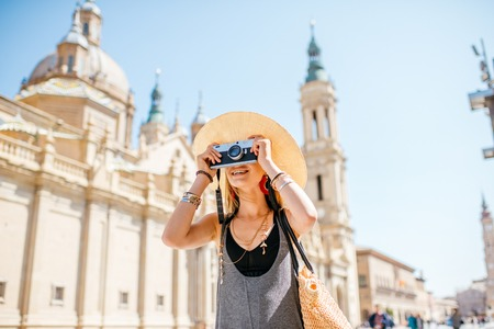 Portrait of a young woman tourist standing with photo camera in front of the famous cathedral on the central square in Zaragoza city, Spain