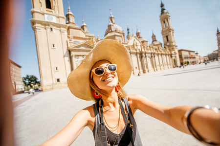 Young woman tourist making selfie photo in front of the famous cathedral on the central square during the sunny weather in Zaragoza city, Spain