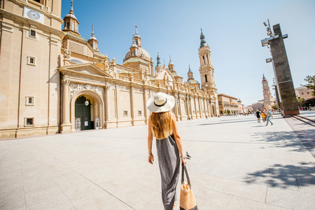 Young woman tourist walking near the famous cathedral on the central square during the sunny weather in Zaragoza city, Spain Stock Photo