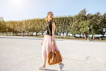 Young business lady walking with bag at the Peyrou park during the morning light in Montpellier city in France Stock Photo