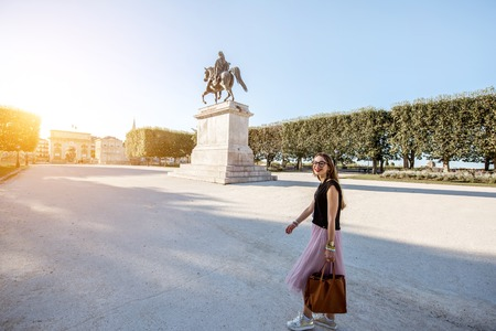 Young business lady walking with bag at the Peyrou park during the morning light in Montpellier city in France. Wide angle view with Louis statue Stock Photo