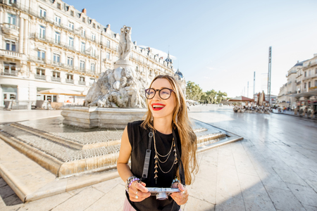 Young woman tourist standing with photo camera on the Comedy square with main fountain on the background in Montpellier city, France