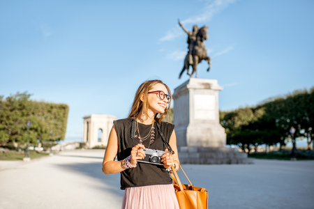 Portrait of a young happy woman tourist at the famous Peyrou park near the Louis statue during the morning light in Montpellier city in France