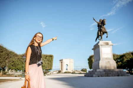 Portrait of a young woman tourist showing Louis statue at the famous Peyrou park during the morning light in Montpellier city in France