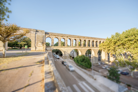 View on the saint Clement aqueduct in Peyrou garden during the morning light in Montpellier city in southern France. Tilt-shift image technic with blurred cars