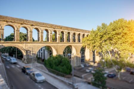 Mening over het aquaduct van heilige Clement in tuin Peyrou tijdens het ochtendlicht in de stad van Montpellier in zuidelijk Frankrijk. Tilt-shift beeldtechniek met wazige auto's Stockfoto