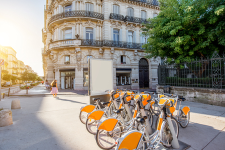 Street view with beautiful old buildings and bicycle parking on the Foch boulevard during the morning light in Montpellier city in France