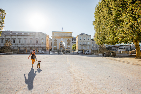 MONTPELLIER, FRANCE - July 28, 2017: View on the beautiful Peyrou promenade with Triumphal arch and woman walking with dog in Montpellier city in France