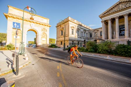 몽펠리에, 프랑스 - 2017 년 7 월 28 일 : 남부 프랑스에서 아침 빛 동안 몽펠리에 도시에서 자전거를 타고 한 아치와 여자 남자와 포크대로에서 볼 에디토리얼