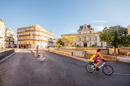 MONTPELLIER, FRANCE - July 28, 2017: City view on Martyrs square with beautiful building and woman riding a bicycle during the morning light in Montpellier city in southern France Editorial