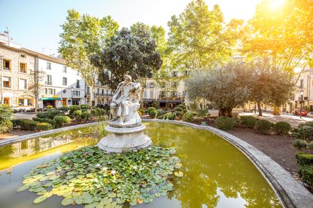 フランス南部の Occitanie 地域のニーム市の小さな緑の噴水の表示します。